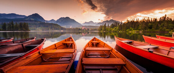 Red boats on Lake Strbske pleso. Morning view of the High Tatras National Park, Slovakia, Europe. Panorama