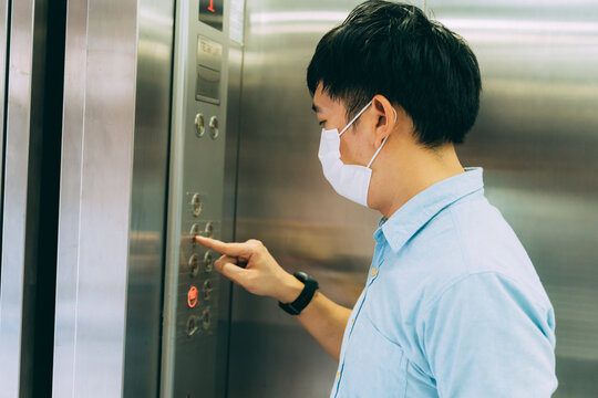 Young Asian businessman wearing protective face mask as precaution against coronavirus standing in elevator pressing floor button to go upstairs