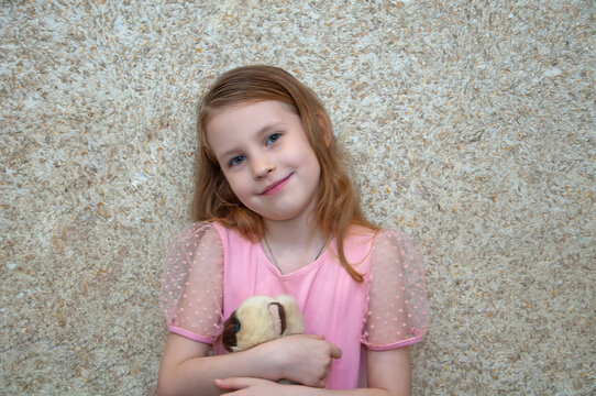 Girl with a soft toy rejoices and laughs.