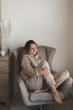 Happy and positive woman with a smile on her face sitting in a cozy armchair at home. Loungewear fashion. Comfort and coziness at home