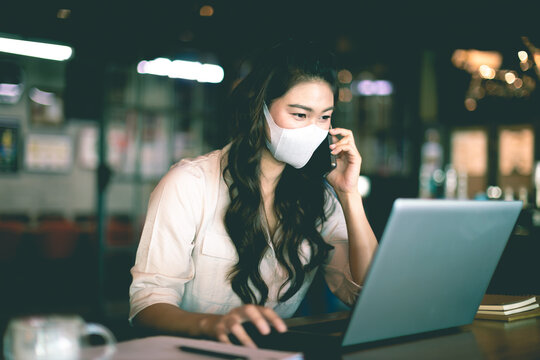 New normal of Asian woman wearing surgical face mask talking with customer work laptop to get ideas and requirement in Business startup at modern office or Co-working space