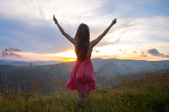 Back view of young happy woman traveler in red dress standing on grassy hillside on a windy evening in summer mountains with outstretched arms enjoying view of nature at sunset.