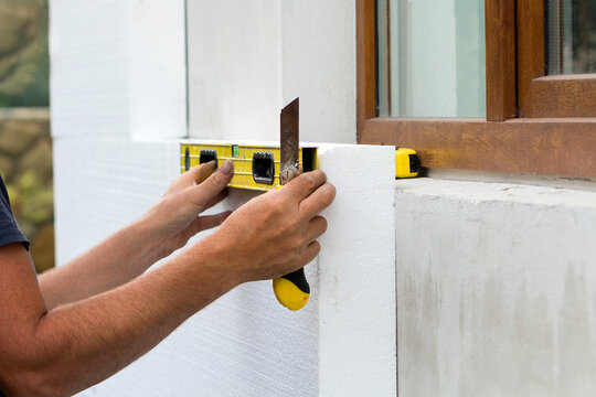 Construction worker insulating house wall with styrofoam insulatuion sheet.