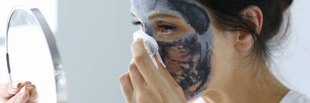 Woman takes off her anti-aging face mask. Home rejuvenation procedures concept