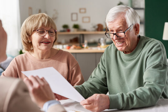 Happy senior couple signing a contract and talking to consultant during meeting at home