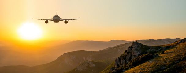 Passenger airliner fly on beauty sunrise or sunset mountain landscape