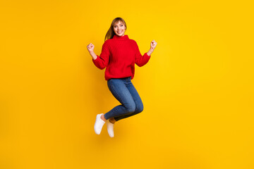 Wall Mural - Full size photo of blond optimistic lady jump hands fists wear red sweater jeans sneakers isolated on bright yellow color background
