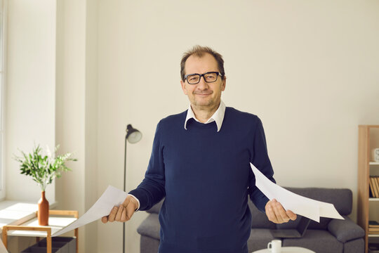 Smiling mature man in eyeglasses standing in his workplace and holding paper documents in both hands. Portrait of happy office worker with business paperwork or college professor with home assignments