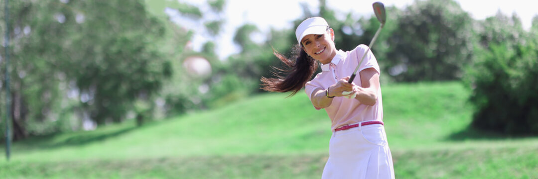 Woman golfer with golf club in hand and flying ball after hitting. Sports and golf concept