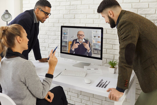 Multiracial business team looking at computer, video calling senior colleague, group mentor or CEO and having online discussion. Mature coach sharing experience with young people in virtual meeting