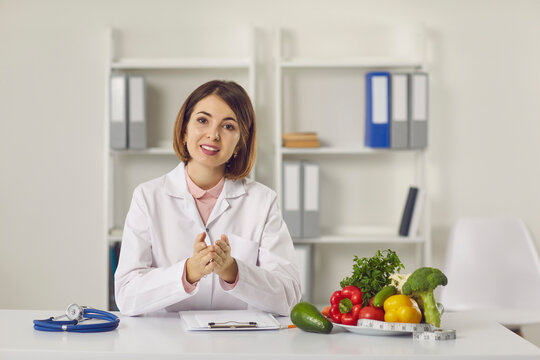 Female nutritionist provides patients with online consultations while sitting in her office. Woman sitting in front of a webcam and talking in a video chat. Concept of proper nutrition.
