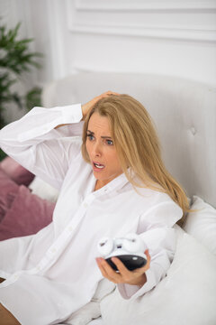 Shocked woman with alarm clock in bed