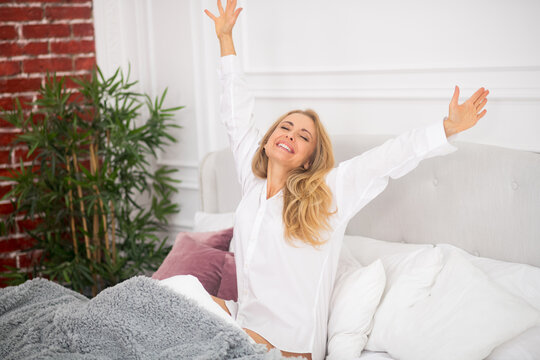 Energetic stretching woman in white bed