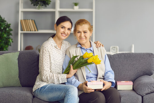 Portrait of daughter and old mother sitting on sofa with gifts and flowers, smiling and looking at camera. Young and senior women enjoying Women's Day. Happy beautiful grandma gets birthday presents