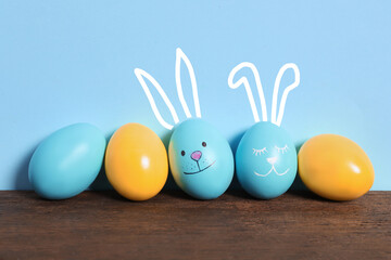 Two eggs with drawn faces and ears as Easter bunnies among others on wooden table against light blue background
