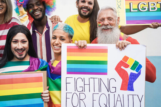 Multiracial gay people having fun at pride parade with LGBT flags and banners outdoors - Focus on bottom faces