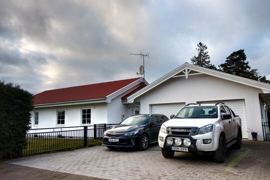 Stockholm, Sweden - May 12, 2019: Two cars parked in driveway near small typical swedish home.