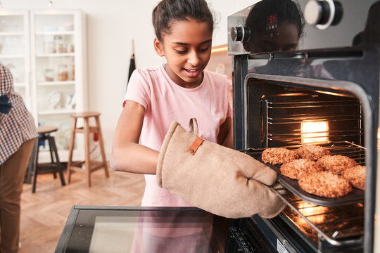 Girl taking tray with cookies out of the oven while baking at the kitchen