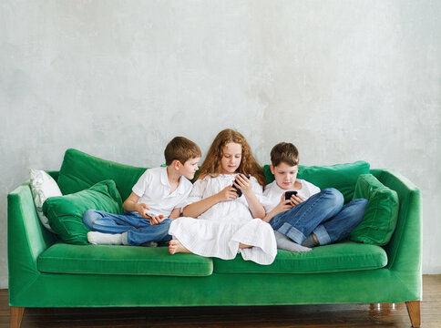 Children play or chat on a smartphone at home on the sofa.