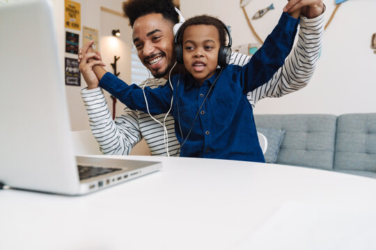 Happy african american father and son in headphones using laptop at home