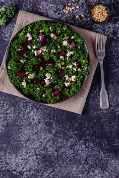 Healthy raw kale and beetroot salad with feta cheese and pine nut.