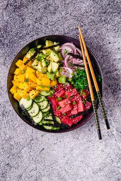 Hawaiian tuna poke bowl with seaweed, avocado, mango, cucumber.