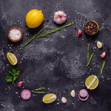 Herbs and condiments on black stone background.