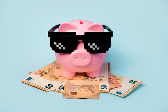 Pink piggy money bank with black sunglasses and euro bills