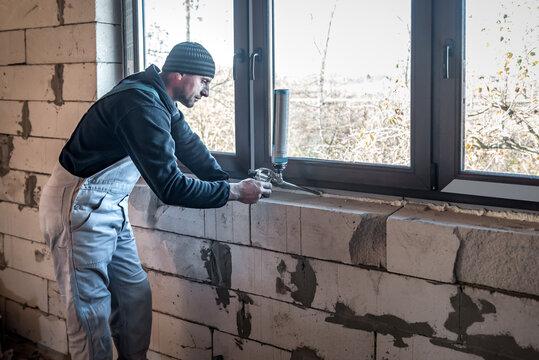 professional builder fixes window with polyurethane foam