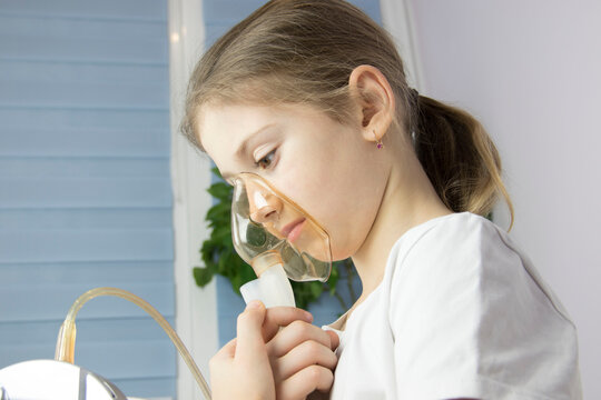 little girl doing inhalation at home with medicines for bronchitis and asthma