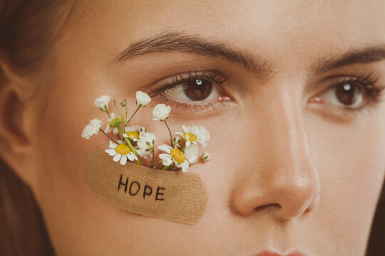 Pretty woman face with Hope inscription on adhesive plaster and spring flowers