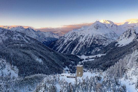 Sunrise on ancient Torre Del Belvedere tower and snowy woods, Maloja, Bregaglia, Engadine, Graubunden Canton, Switzerland, Europe