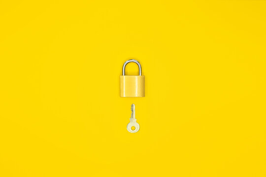 Lock and key on a yellow background.