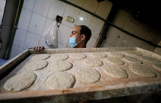 A worker wearing a protective face mask carries dough to be placed in an oven at a bakery amid the coronavirus disease (COVID-19) pandemic in Cairo