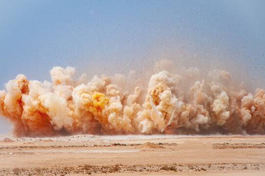 Flying rock and dust clouds during detonator blast on the construction  site