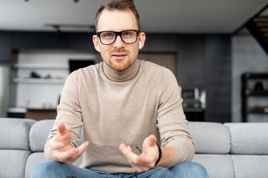 Portrait of intelligent young bearded hipster man looking at camera, wearing glasses and wireless earphones, sitting on a couch in the living room and gesturing. The view while video-calling concept