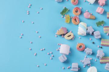 Fototapeta Jellybeans and marshmallow mix on a blue background obraz
