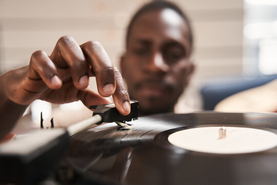 Man putting vinyl record in turntable while sitting on carpet