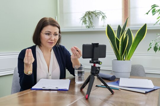Mature confident woman counselor recording video stream, online consultation