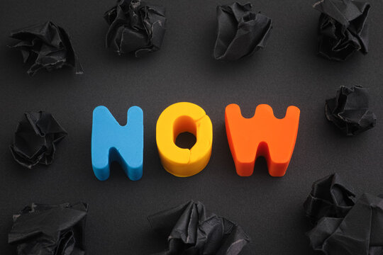 The word Now made out of polymer clay letters with some black crumpled paper balls around it