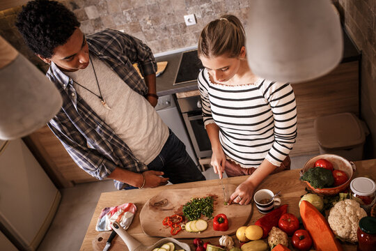 Young couple preparing vegetarian meal.They making fun a the kitchen and preparing vegetables.