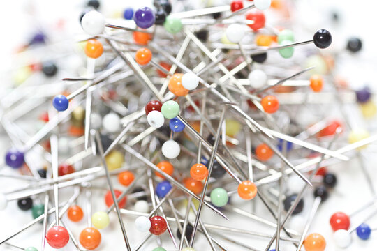Multicolored sewing pins laid loose on white background