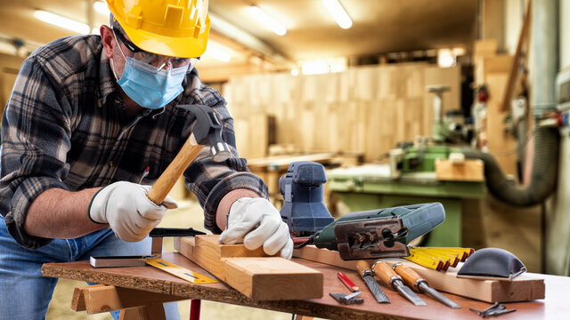 Carpenter worker at work in the carpentry workshop, wears helmet, goggles, leather gloves and surgical mask to prevent coronavirus infection. Preventing Pandemic Covid-19 at the workplace.