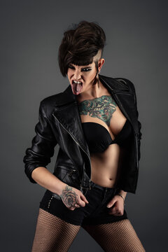 Pretty young tattooed woman, full face, with punk hairstyle, wearing bra, leather jacket, fishnet stockings, sticking out her tongue
