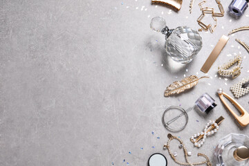 Obraz Flat lay composition with stylish hair clips and perfumes on grey background. Space for text - fototapety do salonu