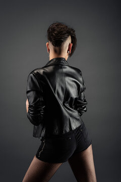 Attractive young woman from back, with punk hairstyle, wearing leather jacket and fishnet stockings