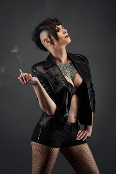 Attractive tattooed young woman, in profile, with punk hairstyle, wearing leather jacket, fishnet stockings, smoking a cigarette