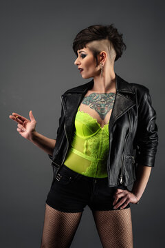 Attractive tattooed young woman, in profile, with punk hairstyle, wearing leather jacket, yellow lace bodysuit, fishnet stockings, holding cirarette in her hand
