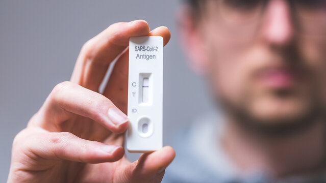 Express corona test at home: Close up of young man holding a negative covid antigen test