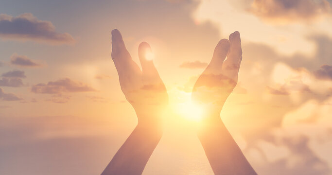 worshiping hands up to the sunset sky. Positive energy, prayer and gratitude concept.
